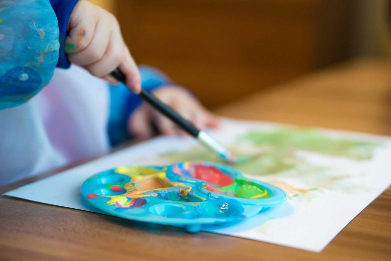 a kid painting with water colors